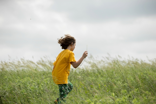 Boy running through a field of wildflowers