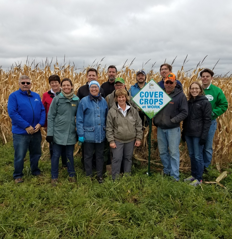"""Minnesota Legislative Agriculture Committee posing at the Becker Farm in front of a sign titled """"Cover Crops"""""""